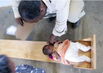 乳児の身長測定。おむつが厚く足を揃えられない