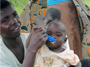 離乳食調理実習で母親が調理した栄養価の高い離乳食を食べる子ども